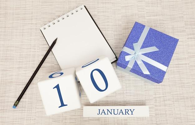 Kalender mit trendigen blauen text und zahlen für den 10. januar und ein geschenk in einer box Premium Fotos