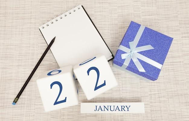 Kalender mit trendigen blauen text und zahlen für den 22. januar und ein geschenk in einer box Premium Fotos