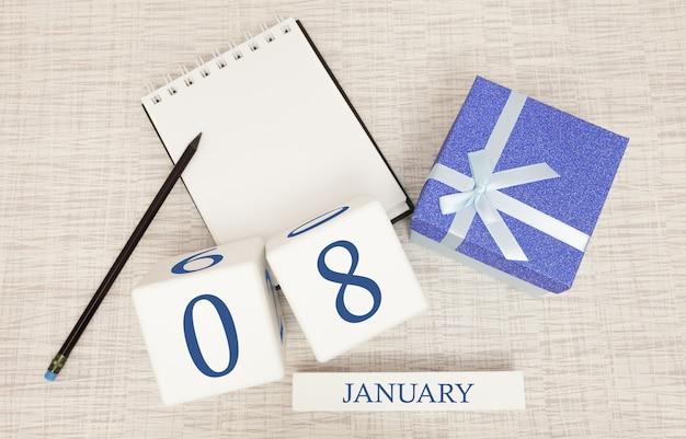 Kalender mit trendigen blauen text und zahlen für den 8. januar und ein geschenk in einer box Premium Fotos