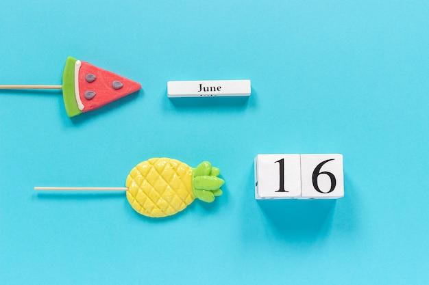 Kalenderdatum 16. juni und sommer früchte süßigkeiten ananas, wassermelone lutscher. Premium Fotos