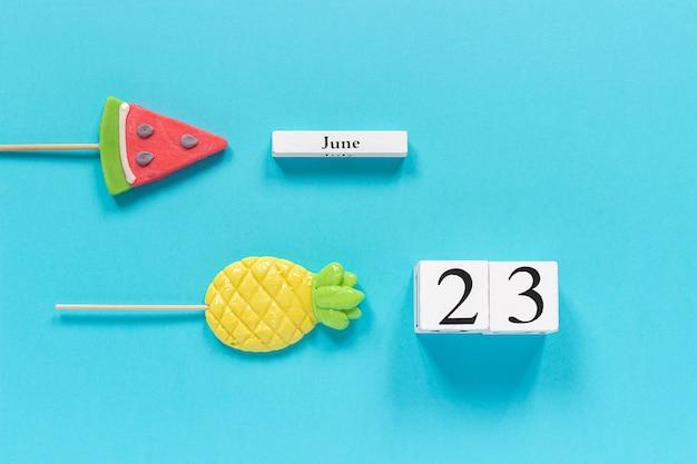Kalenderdatum 23. juni und sommerfrüchte süßigkeiten ananas, wassermelonen lutscher Premium Fotos