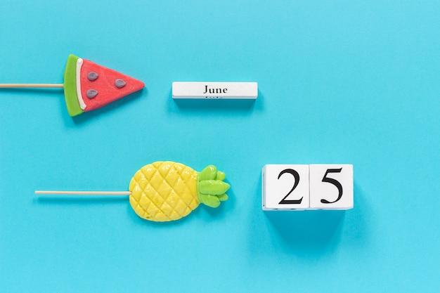 Kalenderdatum 25. juni und sommer früchte süßigkeiten ananas, wassermelone lutscher. Premium Fotos