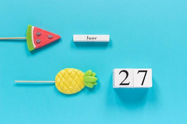 Kalenderdatum 27. juni und sommer früchte süßigkeiten ananas, wassermelone lutscher. Premium Fotos