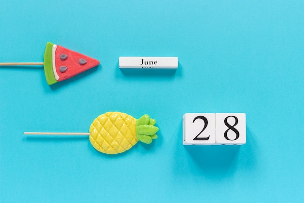 Kalenderdatum 28. juni und sommer früchte süßigkeiten ananas, wassermelone lutscher Premium Fotos