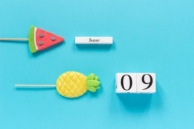 Kalenderdatum 9. juni und sommer früchte süßigkeiten ananas, wassermelone lutscher. Premium Fotos