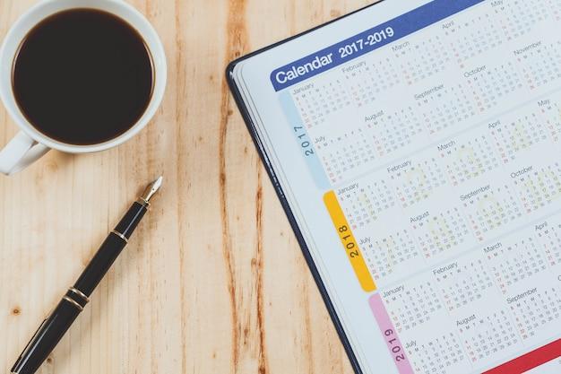 Kalenderplaner mit füllfederhalter und heißer kaffee auf hölzerner tabelle bürowerkzeug. Premium Fotos