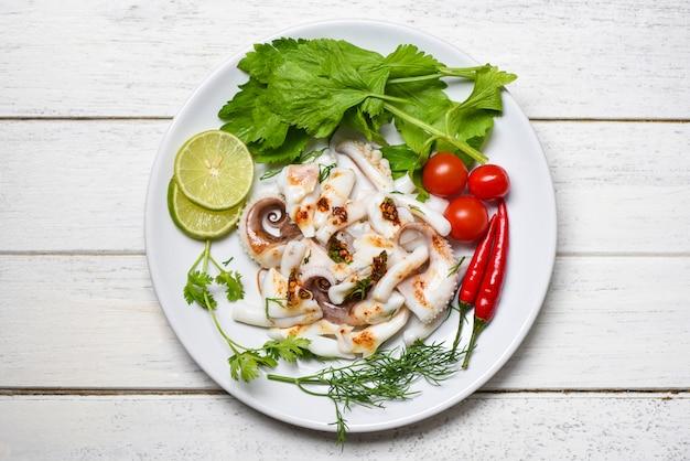 Kalmarsalat mit zitronenkräutern und -gewürzen auf draufsicht des hölzernen hintergrundes tentakelkrake kochte die heißen und würzigen paprikasoßenmeeresfrüchte des aperitiflebensmittels, die auf weißer platte im restaurant gedient wurden Premium Fotos