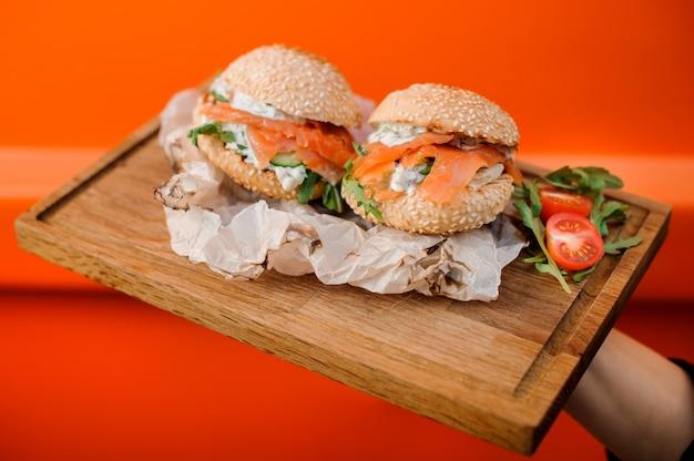 Kalte burger mit lachs, soße, gurke, tomate und rucola dienten in der hölzernen platte Premium Fotos