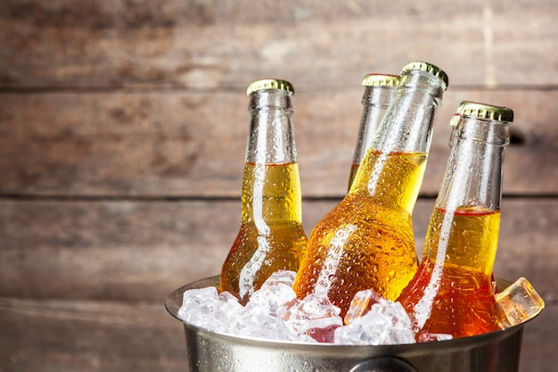 Kalte flaschen bier im eimer auf hölzernem Premium Fotos