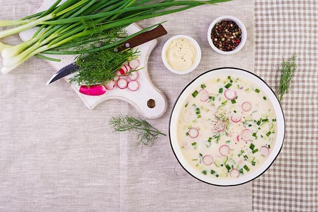 Kalte suppe mit frischen gurken, radieschen, kartoffeln und wurst mit joghurt in der schüssel Kostenlose Fotos