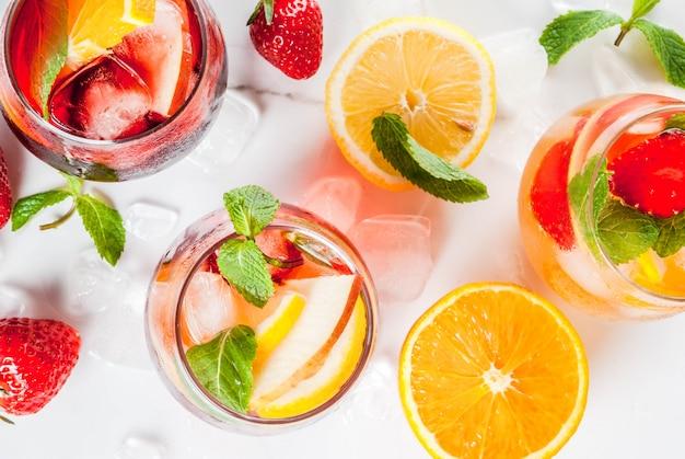 Kalte weiße, rosa und rote sangriacocktails mit frischen früchten, beeren und minze Premium Fotos