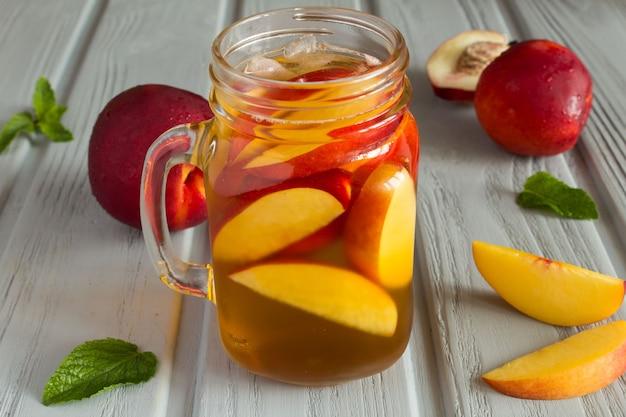 Kalter tee mit pfirsich und früchten auf der grauen holzoberfläche Premium Fotos