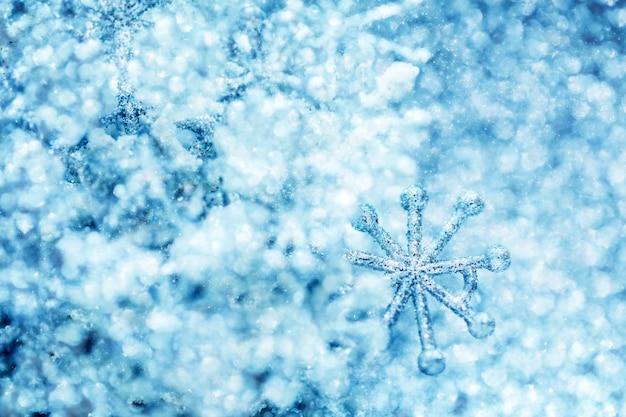 Kalter winterfunkelnhintergrund mit schneeflocke Premium Fotos