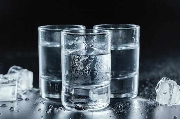 Kalter wodka in den schnapsgläsern auf schwarzem Premium Fotos