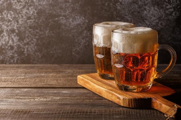 Kaltes bier in glas mit pommes auf einer dunklen oberfläche Premium Fotos