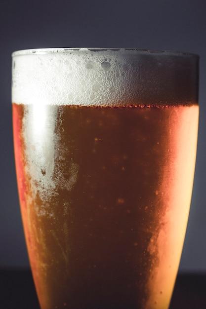 Kaltes bierglas auf einem dunklen hintergrund auf holztisch Premium Fotos