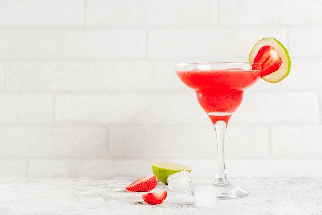 Kaltes erdbeer-margarita-cocktail mit eis, limette und frischen beeren im margarita-glas Premium Fotos