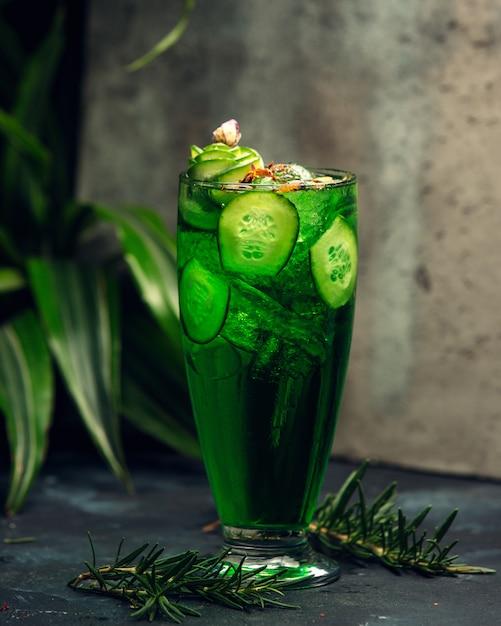 Kaltes grünes getränk in einem glas mit geschnittenen gurkenscheiben Kostenlose Fotos