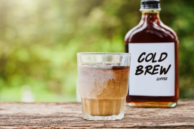 Kaltgebrühter kaffee mit milch auf einem tisch draußen mit kaltgebrühtem kaffee in einer glasflasche zum mitnehmen Premium Fotos