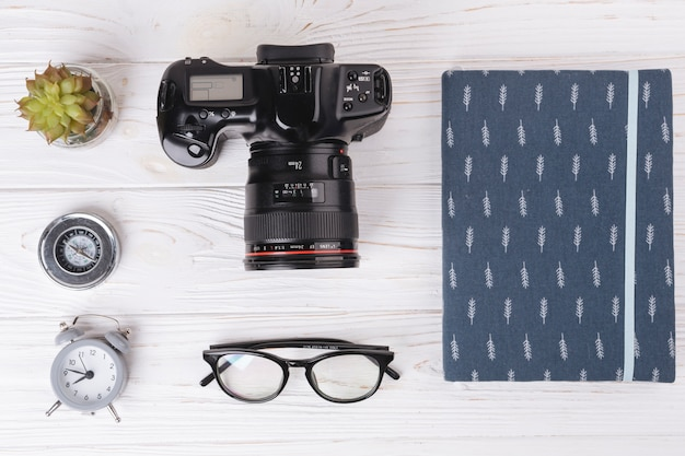 Kamera mit notizbuch auf holztisch Kostenlose Fotos