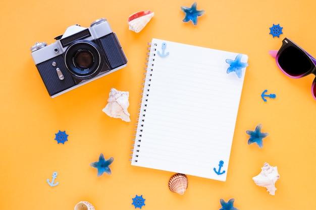 Kamera mit sonnenbrille, muscheln und leerem notizbuch Kostenlose Fotos