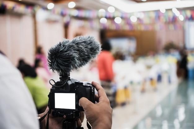 Kameramann video oder professioneller digitaler spiegel ohne stativ für kameraaufnahmen mit mikrofon Premium Fotos