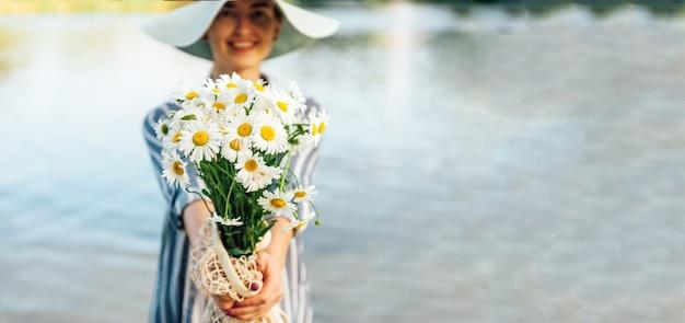 Kamillenblumenstrauß in den händen des mädchens auf fluss. Premium Fotos