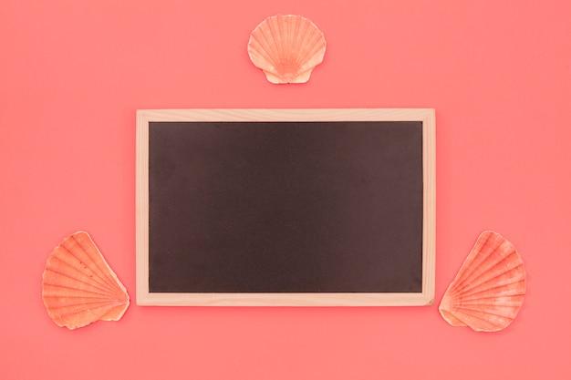 Kammmuschelmuschel nahe der hölzernen leeren tafel gegen den korallenroten hintergrund Kostenlose Fotos