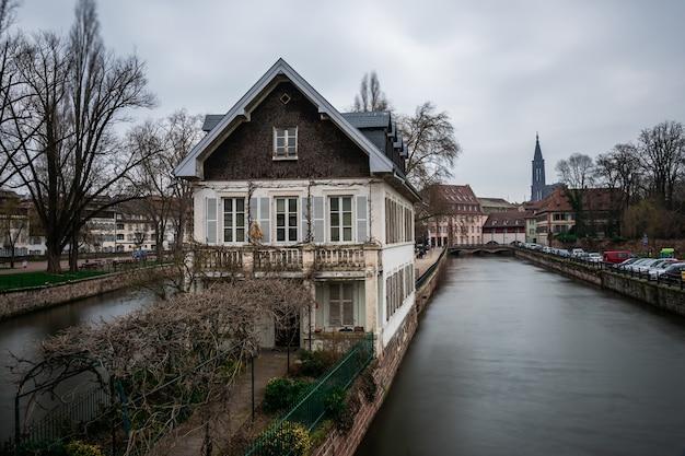 Kanal umgeben von gebäuden und grün unter einem bewölkten himmel in straßburg in frankreich Kostenlose Fotos