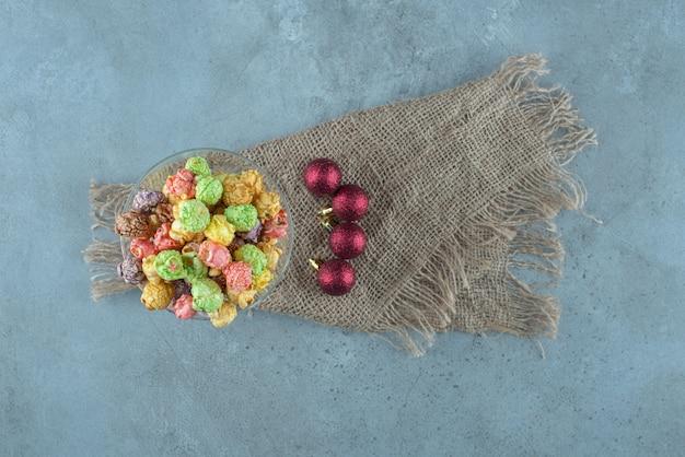 Kandiertes popcorn gestapelt in einem glashalter neben weihnachtskugeln auf marmoroberfläche Kostenlose Fotos