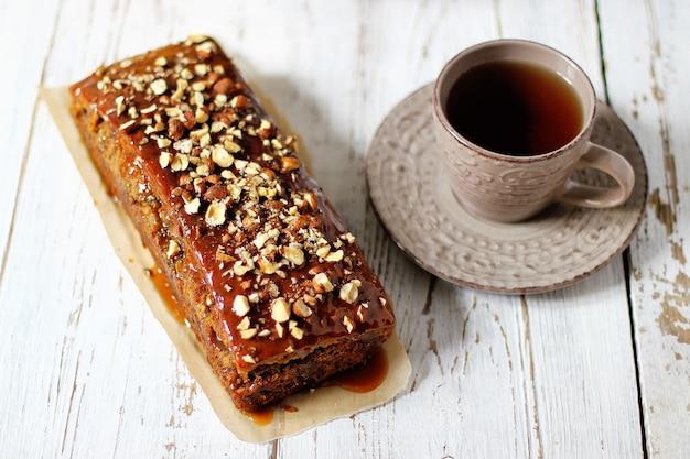 Karamelltortenkuchen mit hackfleischnüssen und einer tasse tee Kostenlose Fotos