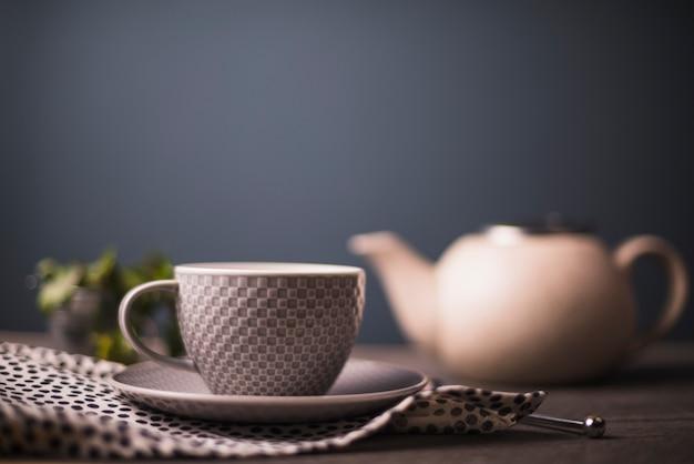 Karierte musterteeschale auf polka punktiertem gewebe auf tabelle Kostenlose Fotos