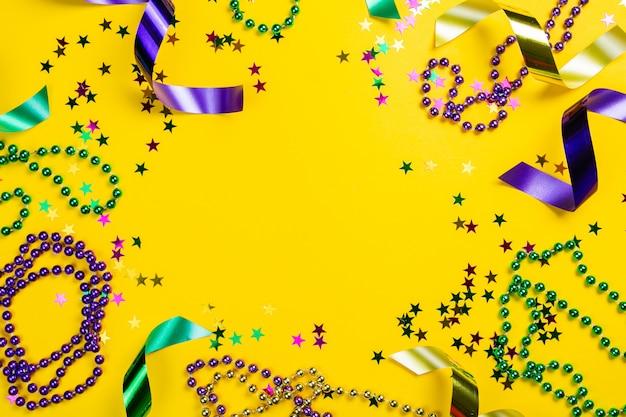 Karnevalkarnevalkonzept - perlen auf gelbem hintergrund, draufsicht Premium Fotos