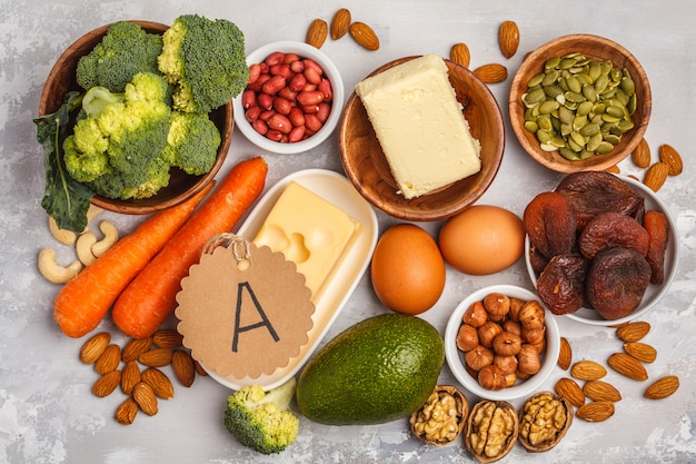 Karotten, nüsse, brokkoli, butter, käse, avocado, aprikosen, samen, eier. weißer hintergrund, ansicht von oben Premium Fotos
