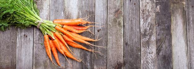 Karottenbündel auf einem hölzernen hintergrund, rustikaler stil Premium Fotos