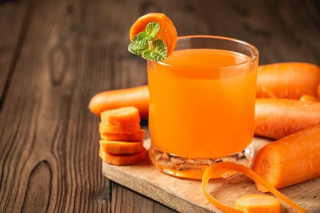 Karottensaft im glas auf holztisch. Kostenlose Fotos
