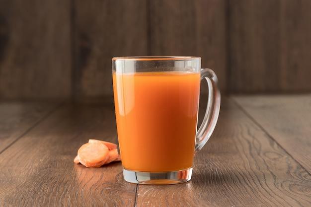 Karottensaft in einem glas auf holz Premium Fotos