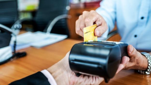 Kartenzahlungen zwischen geschäftsleuten über kreditkartenautomaten im büro. Premium Fotos