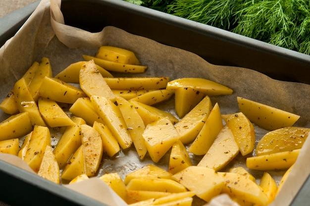 Kartoffel brät scheiben im backpapier und im grünen dill Premium Fotos