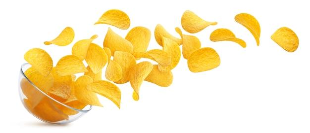 Kartoffelchips, die in die glasschüssel lokalisiert auf weißem hintergrund fallen Premium Fotos