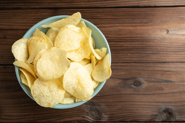 Kartoffelchips in der schüssel auf einem holztisch. Kostenlose Fotos