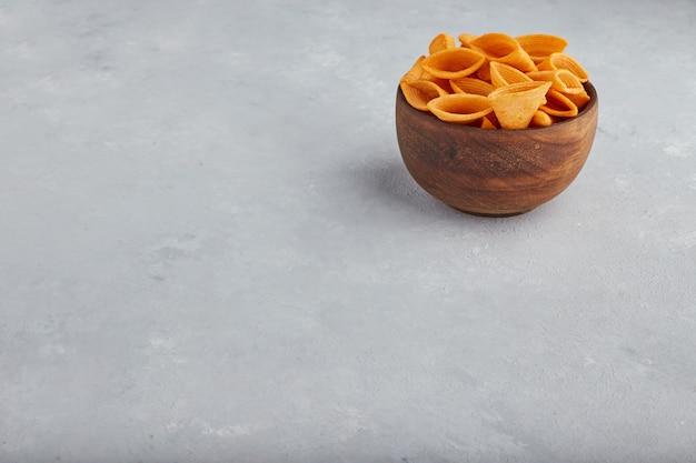 Kartoffelchips in holzschale in der oberen ecke. Kostenlose Fotos