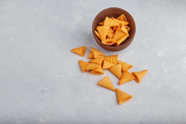 Kartoffelchips verteilen sich auf der weißen oberfläche aus der holzschale. Kostenlose Fotos