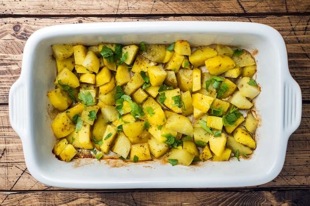 Kartoffeln gebacken mit gewürzen und kräutern in einem keramischen backblech. vegetarische küche Premium Fotos
