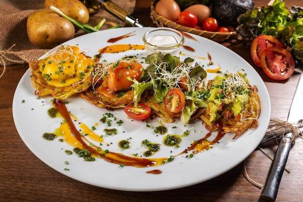Kartoffelpuffer mit spiegeleiern, speck und gemüse zum frühstück Premium Fotos