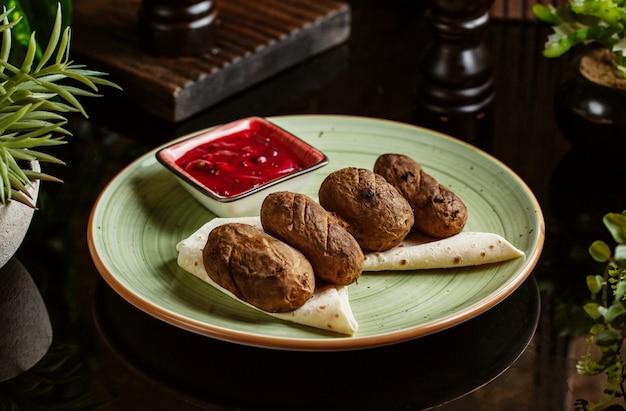 Kartoffelspiess serviert auf fladenbrot mit saurer sauce Kostenlose Fotos