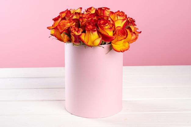 Karton mit rosen auf rosa hintergrund Premium Fotos