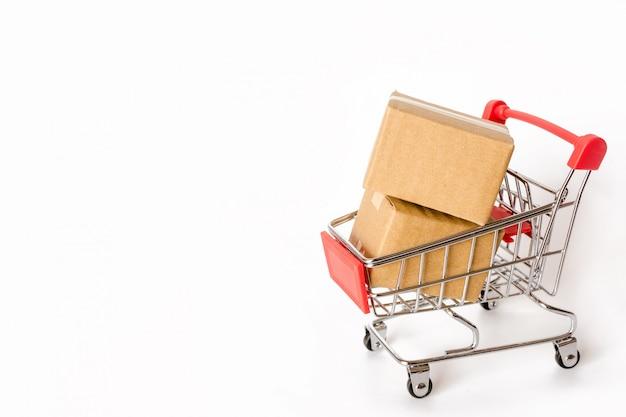 Kartons oder papierkästen im roten warenkorb auf weißem hintergrund. mit textfreiraum Premium Fotos