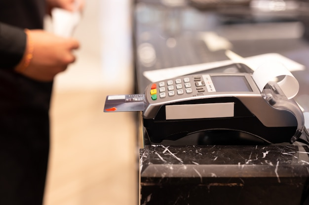 Kassierer, der kreditkartenmaschine für kundeneinkaufszahlung im speicher verwendet. Premium Fotos