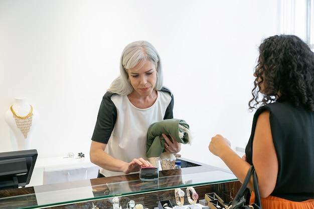 Kassierer oder verkäufer, der den zahlungsvorgang mit pos terminal und kreditkarte durchführt. kunde bezahlt stoff an der kasse. einkaufs- oder kaufkonzept Kostenlose Fotos
